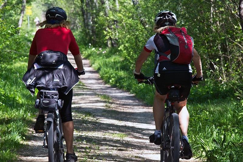 Två som cyklar mountainbike på en väg